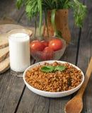 Papa de aveia do trigo mourisco com um ramo da salsa em uma bacia, com um vidro do leite e dos tomates em uma tabela de madeira à fotografia de stock