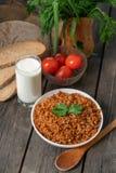 Papa de aveia do trigo mourisco com um ramo da salsa em uma bacia, com um vidro do leite e dos tomates em uma tabela de madeira à fotos de stock