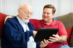 Papa de enseignement pour utiliser le PC de tablette Images stock