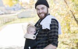 Papa de Millenial avec le bébé dans la marche extérieure de transporteur photo stock