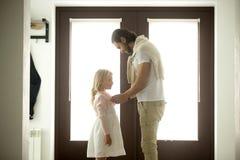 Papa de soin s'habillant boutonnant la petite fille à la maison, bon fath Photos stock