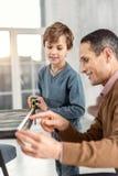 Papa de sourire aidant son fils à mesurer la table Photographie stock libre de droits