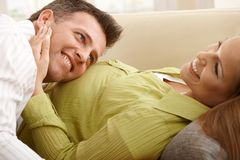 Papa die aan baby in buik luistert Royalty-vrije Stock Afbeelding