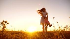 Papa die klein kind omcirkelen bij zonsondergang, het gelukkige papa spelen met een kleine dochter stock videobeelden