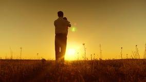 Papa die klein kind omcirkelen bij zonsondergang, het gelukkige papa spelen met een kleine dochter, Langzame motie stock video