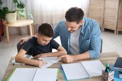 Papa die zijn zoon met thuiswerk helpen royalty-vrije stock fotografie