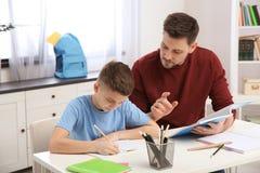 Papa die zijn zoon met thuiswerk helpen stock foto
