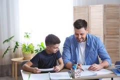Papa die zijn zoon met thuiswerk helpen stock afbeeldingen