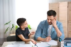 Papa die zijn zoon met thuiswerk helpen royalty-vrije stock afbeelding