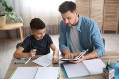 Papa die zijn zoon met thuiswerk helpen stock afbeelding