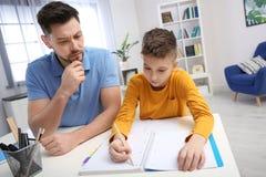 Papa die zijn zoon met thuiswerk helpen royalty-vrije stock foto