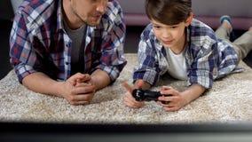 Papa die zoon adviseren hoe te om videospelletjebedieningshendel, steun en zorg, vrije tijd in werking te stellen royalty-vrije stock fotografie