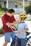 Papa die zoon met helm helpt Stock Afbeelding