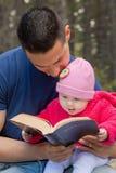 Papa en Baby de Bijbel van de Dochterlezing Stock Afbeeldingen