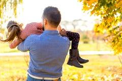 Papa en dochter in het spel van het de herfstpark het lachen royalty-vrije stock foto's