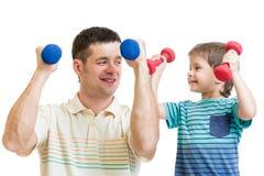 Papa en jong geitjezoon die oefening met domoren doen stock foto