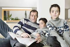 Papa en jonge geitjes die tijdschrift lezen Stock Afbeelding