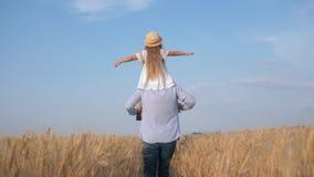 Papa en kind het meisjesspel in openlucht, gelukkige vader vervoert weinig dochter in strohoed en witte kleding op zijn schouders stock videobeelden