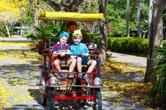 Papa en twee kleine jong geitjejongens die op fiets biking Stock Foto's