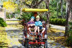 Papa en twee kleine jong geitjejongens die op fiets biking Royalty-vrije Stock Afbeeldingen