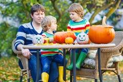 Papa en twee kleine zonen die hefboom-o-lantaarn maken voor Halloween in a Stock Afbeelding