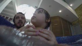 Papa en weinig zoon die in de binnenpool zwemmen stock footage