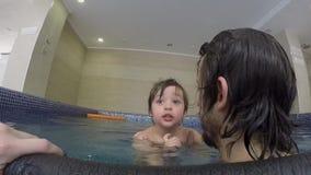 Papa en weinig zoon die in de binnenpool zwemmen stock video