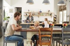 Papa en zoon bij keukenlijst, mum en dochter op achtergrond stock foto