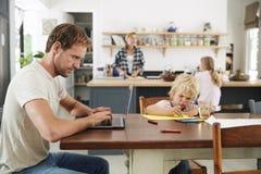 Papa en zoon bij keukenlijst, mum en dochter op achtergrond royalty-vrije stock foto