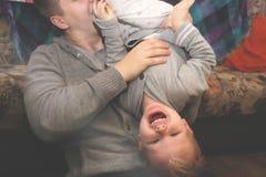 Papa en zoons het spel, stelt tevreden De vader draaide zijn zoonsbovenkant - neer, de kindlach royalty-vrije stock fotografie