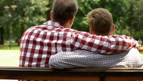 Papa en zoons omhelzen, die op bank in park, relaties zitten van steun en vertrouwen stock afbeeldingen