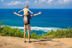 Papa en zoonsreizigers op een klip boven het strand Leeg paradijsstrand, blauwe overzeese golven in het eiland van Bali, Indonesi royalty-vrije stock fotografie