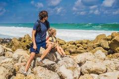 Papa en zoonsreizigers op verbazend Melasti-Strand met turkoois water, het Eiland Indonesië van Bali Het reizen met jonge geitjes stock fotografie