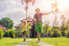 Papa en zoonstoeristen in Traditionele Balinese Hindoese Tempel Taman Ayun in Mengwi Bali, Indonesië Het reizen met kinderenconce stock foto's