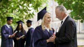Papa enthousiaste félicitant la fille licenciée en parc près de l'académie, bonheur photos stock