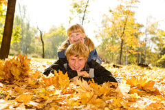 Papa et descendant sur des lames d'automne Photos stock
