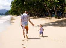 Papa et descendant sur la plage Images libres de droits