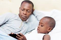 Papa et enfant dans le lit images stock