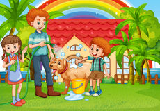 Papa et enfants donnant à chien un bain Photo stock