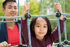 Papa et fille asiatiques sur le terrain de jeu Photographie stock libre de droits