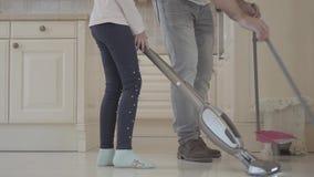 Papa et fille ayant l'amusement dans une maison propre Un homme avec le balai et la pelle à poussière et fille avec un aspirateur clips vidéos