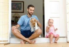 Papa et fille et leur chien Un homme et une fille près de sa maison sur le porche À côté de eux leur animal familier Image stock
