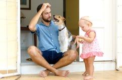 Papa et fille et leur chien Un homme et une fille près de sa maison sur le porche À côté de eux leur animal familier Photos stock