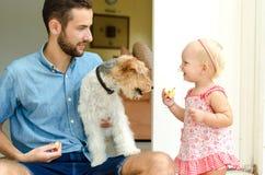 Papa et fille et leur chien Un homme et une fille près de sa maison sur le porche À côté de eux leur animal familier Photo libre de droits