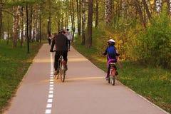 Papa et fille sur des bicyclettes en parc Photos libres de droits