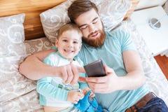 Papa et fils à l'aide du téléphone portable sur le lit ensemble Images libres de droits