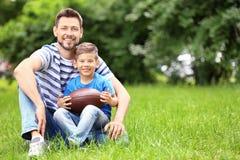 Papa et fils avec la boule de rugby Images stock