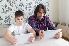 Papa et fils avec la tablette d'intérieur photo stock