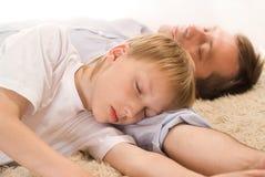 Papa et fils dormant sur le tapis Photo libre de droits