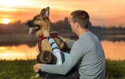 Papa et fils et berger allemand en nature observant le coucher du soleil Image stock